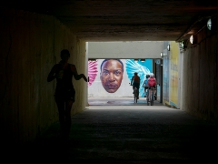 A Mural Featuring the Face of an African American Man Highlighted As A Jogger and Bikers Ride Past. Image by Michael Bracey